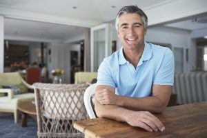 Portrait of a handsome mature man sitting at a table in his home