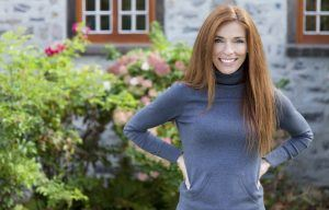 Mature red hair female with blue sweater in garden