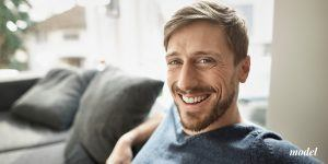 Male with beard sitting on a couch smiling